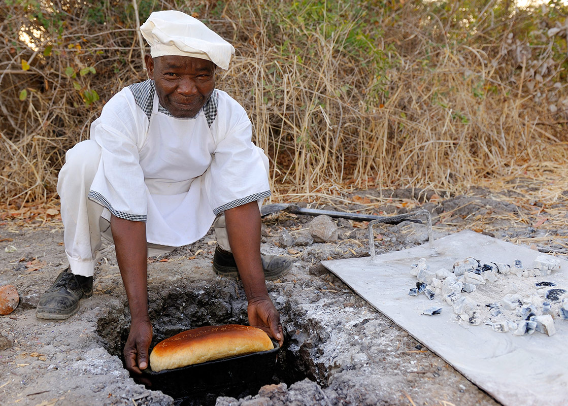 Remote Africa Safaris chef making bread over a wood fire at Crocodile Camp in Zambia
