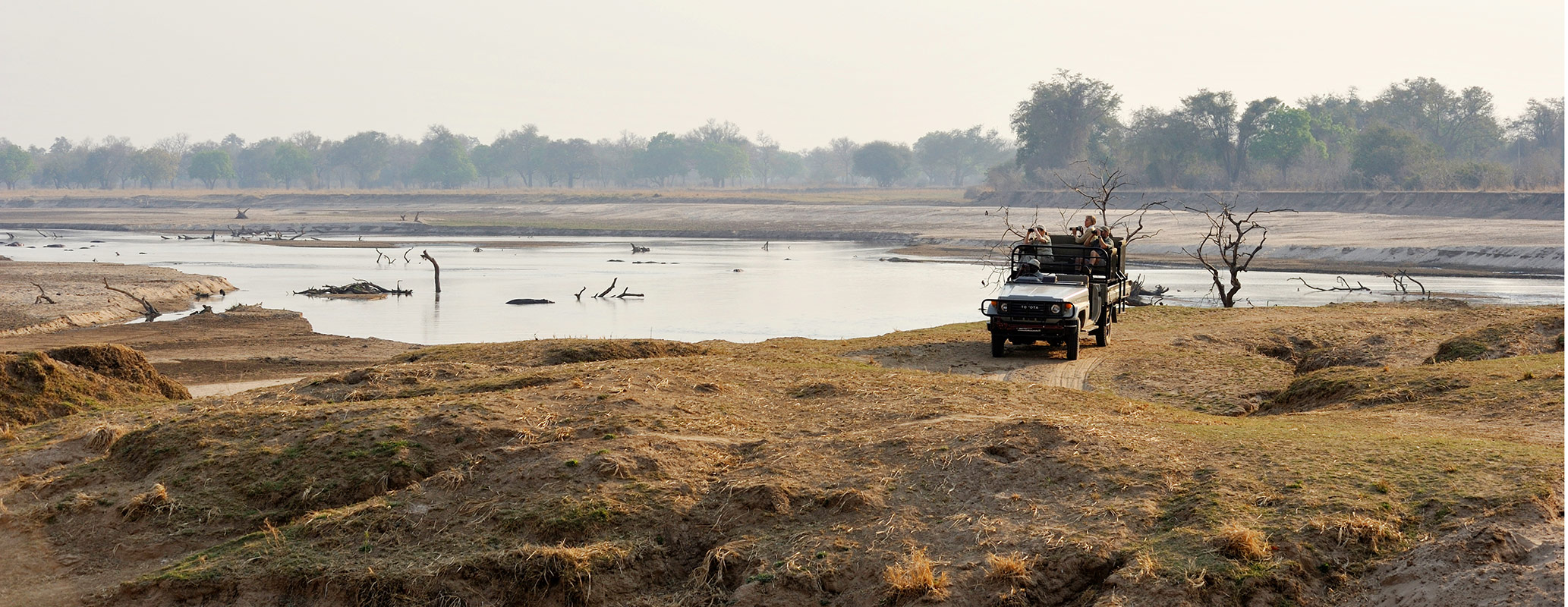 Remote Africa Safaris guests on a game drive past the Luangwa river in Zambia
