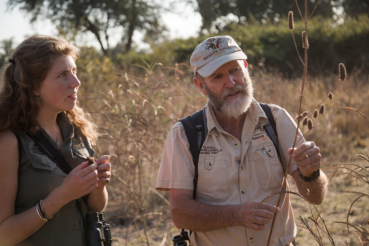 Remote Africa Safaris guide, Brian Jackson, informs a guest of the diverse plant life in the Luangwa Valley during a walking safari on the Chikoko Trails in Zambia