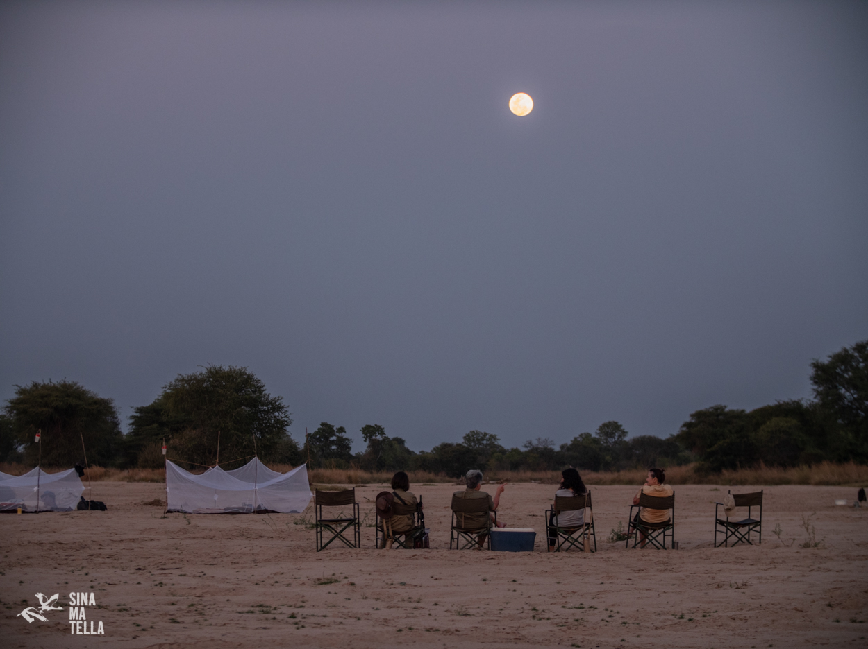 Guests at Remote Africa Safaris, enjoying a night cap under the full moon on the bank of the Mwaleshi river