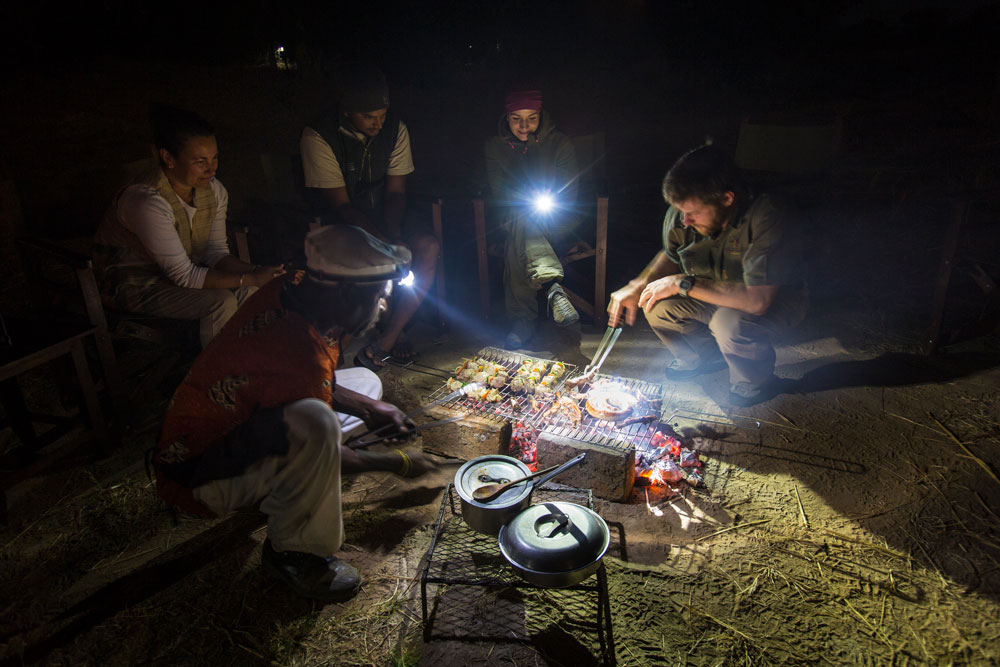 Guests at Remote Africa Safaris looking on as Safari Guide, Brent Harris, prepare their dinner over the open flames of a raw wood fire.