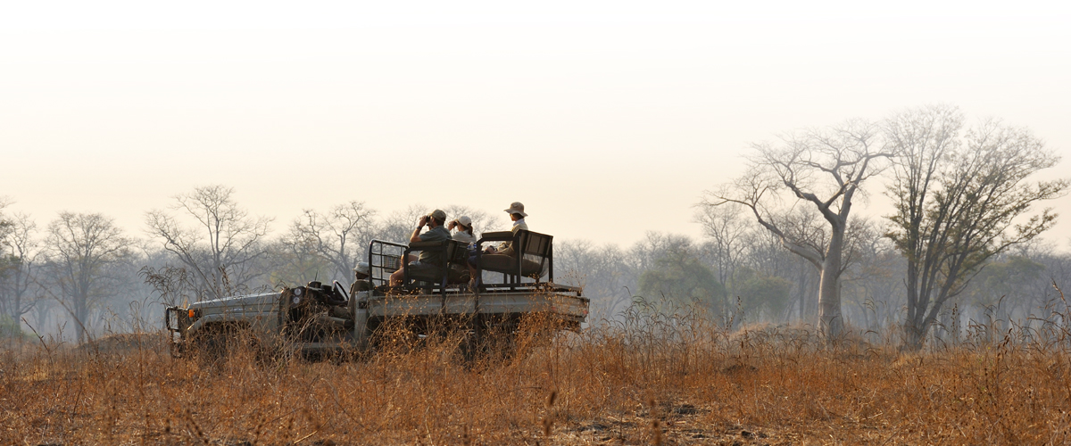Guests of Tafika Camp on the back of a safari vehicle during a game drive in South Luangwa, Zambia
