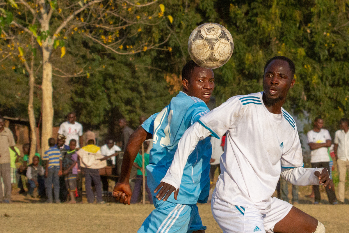 Two footballers from the Football for Wildlife league, competing for the ball.